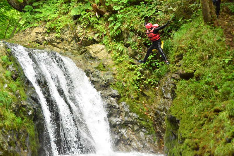 キャニオニングで滝壺に向かってジャンプする人