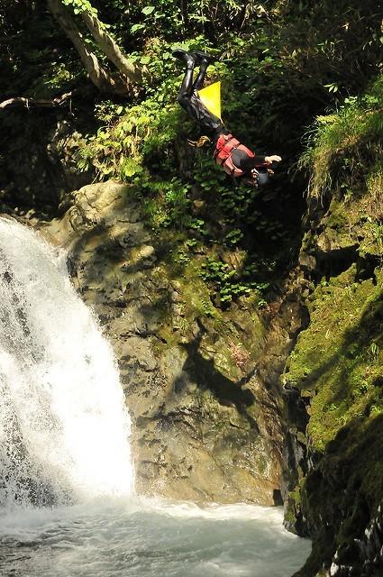 ニセコの川で滝壺に向かってダイブする人