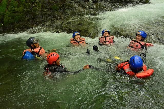 キャニオニングで手を繋いで川面に浮いて遊ぶ人たち(ニセコ)