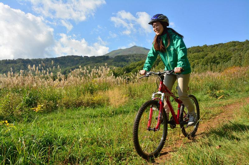 秋のニセコでサイクリングを楽しむ女性