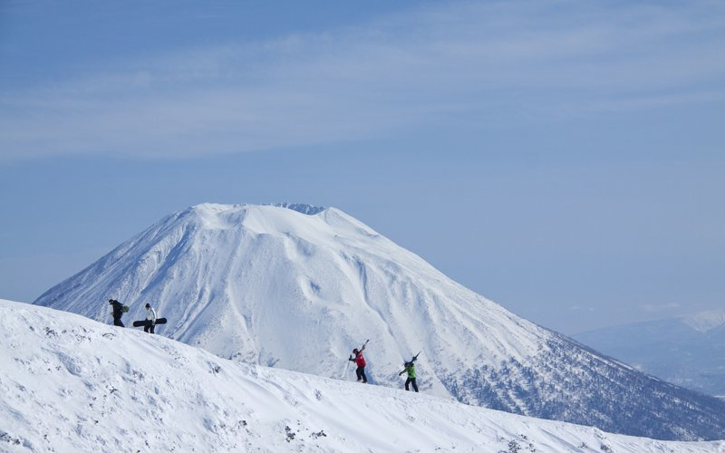backcountry skiers and snowboarders hiking in niseko