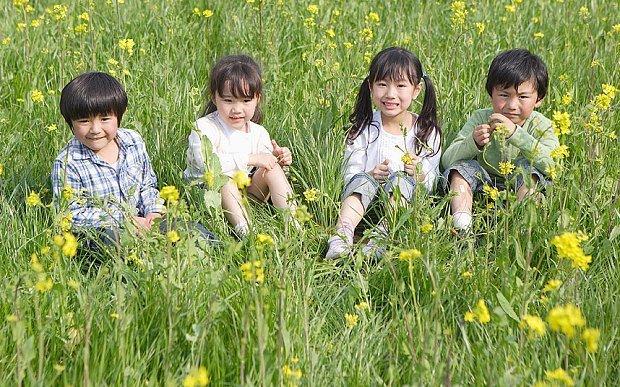 children sitting in a flower field looking happy. children's day japan 2020 golden week