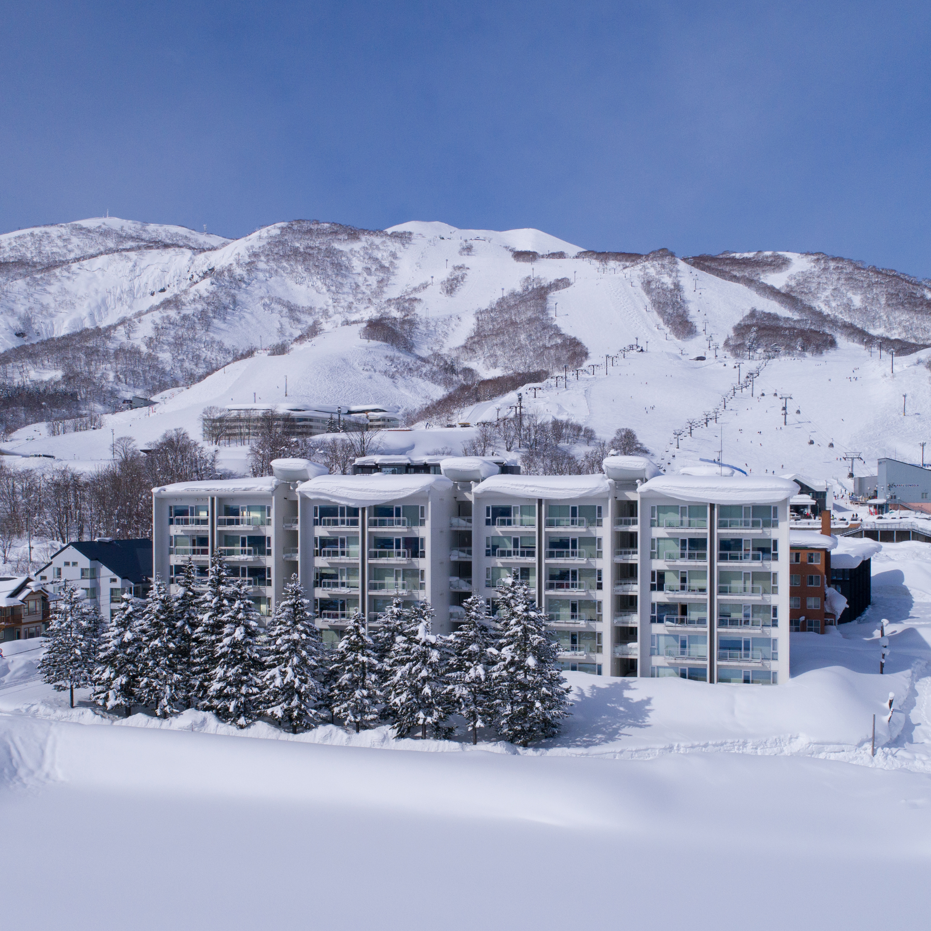 Snowy exterior of Niseko Landmark View apartments with Mt Niseko Annupuri Ski Hill in the background.