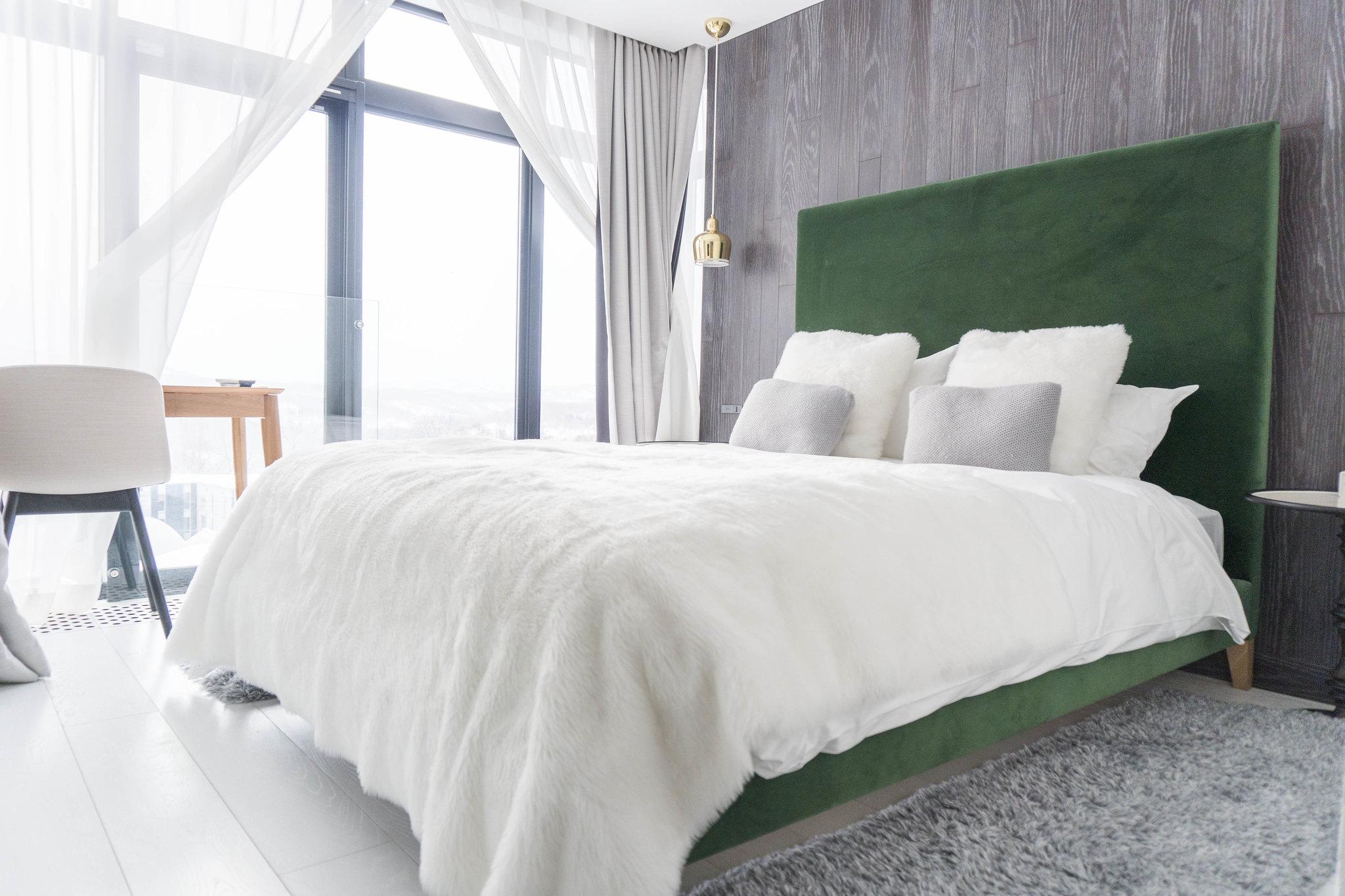 A plush queen bed with green backboard in a warm bedroom in LOFT Niseko.