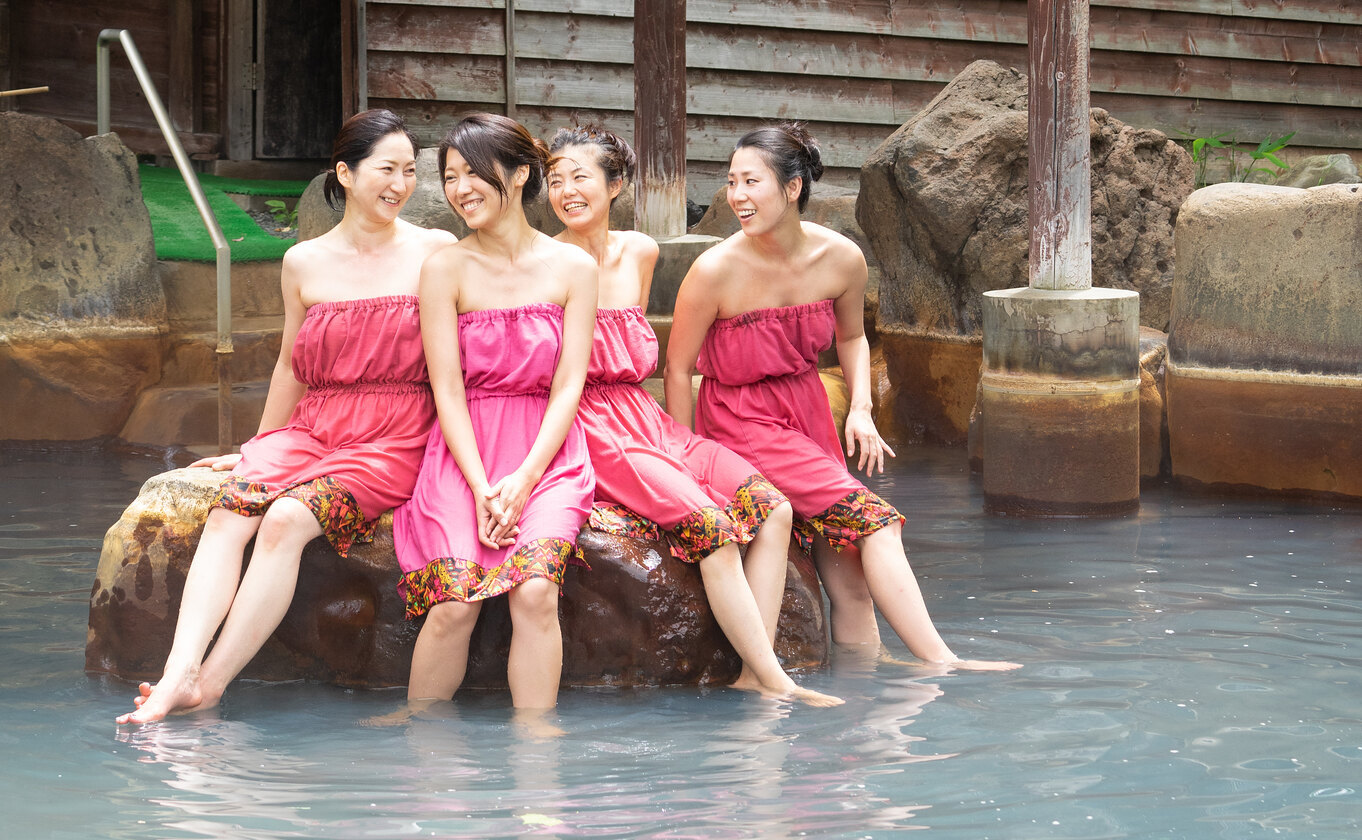 A group of 4 women wearing modesty dresses in a mixed onsen at Niseko Grand Hotel.