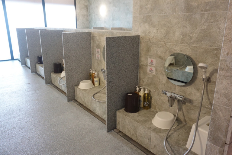 The showering area of an indoor onsen in Niseko with a mirror, shower, stool, soap and wash basin.