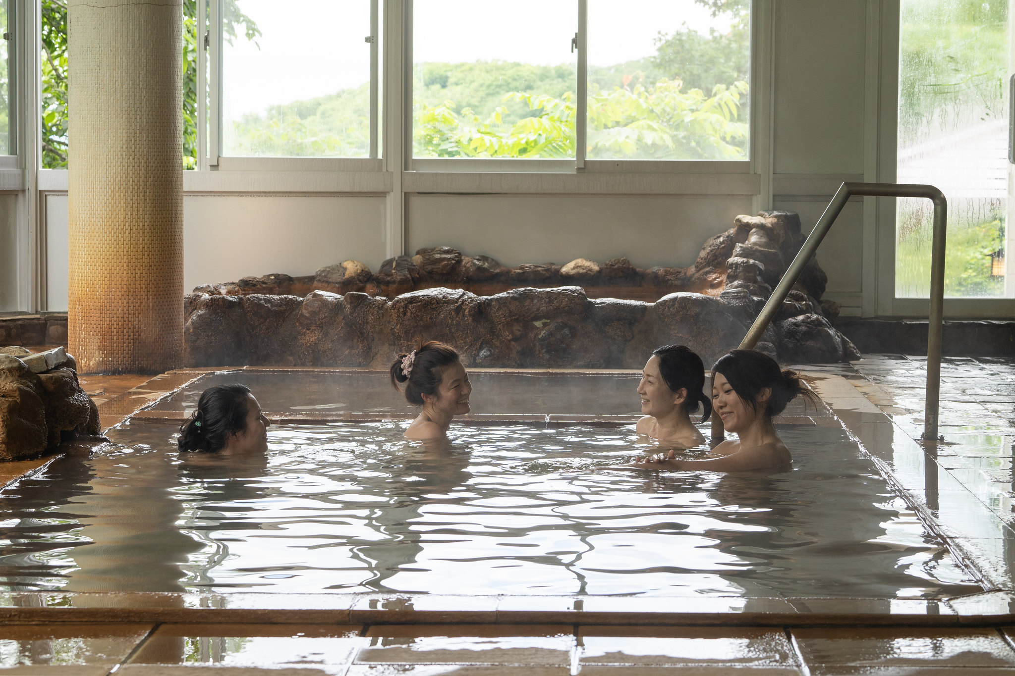A group of 4 women chatting in an indoor onsen at Niseko Grand Hotel in Japan.