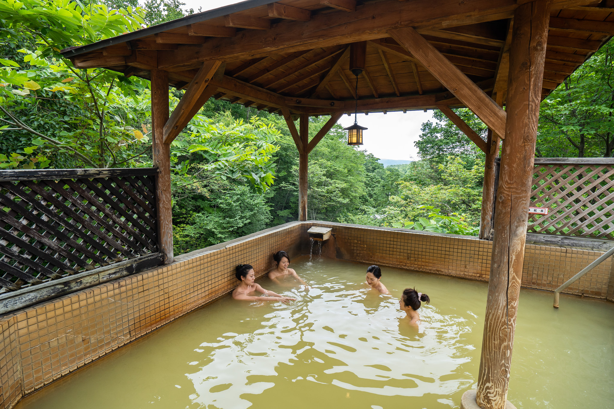 4 women bathing in an outdoor onsen in Summer at the Grand Hotel in Niseko, Japan.
