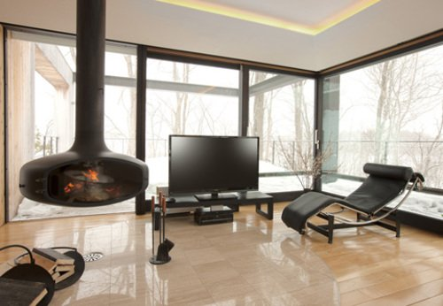 The living room with lounge chair, snow views and fireplace at Glasshouse in Niseko.