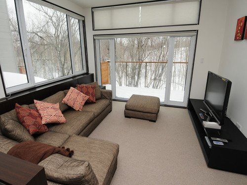 The living room with snow views in a 4 bedroom townhouse at Neyuki Townhouses in Niseko, Japan.