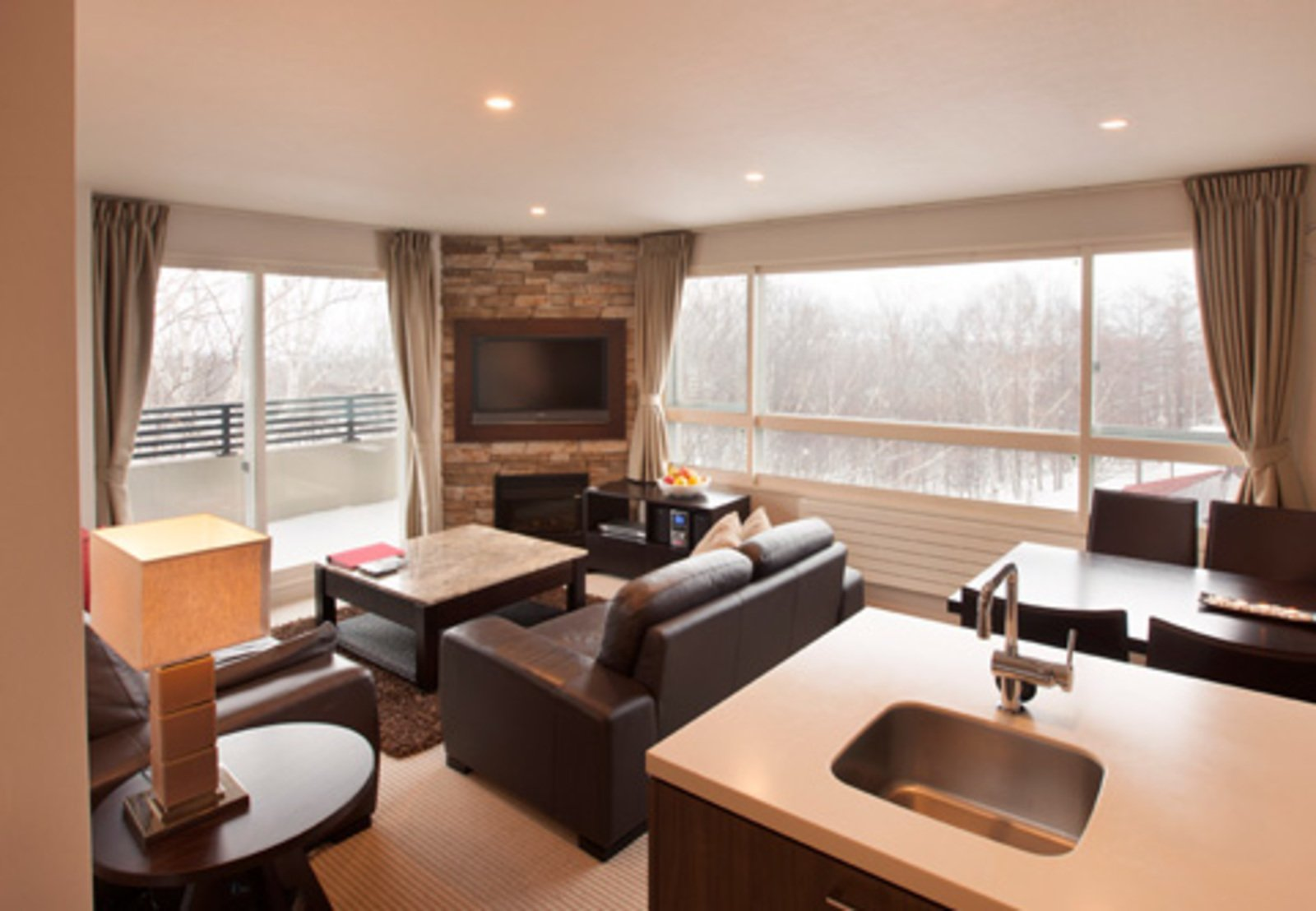 The kitchen and living area of a 1 bedroom apartment with snow views at Freshwater Niseko.
