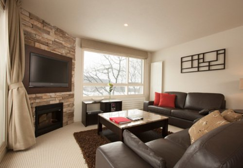 The living area with fireplace, TV and mountain views in a 3 bedroom apartment at Freshwater in Niseko.