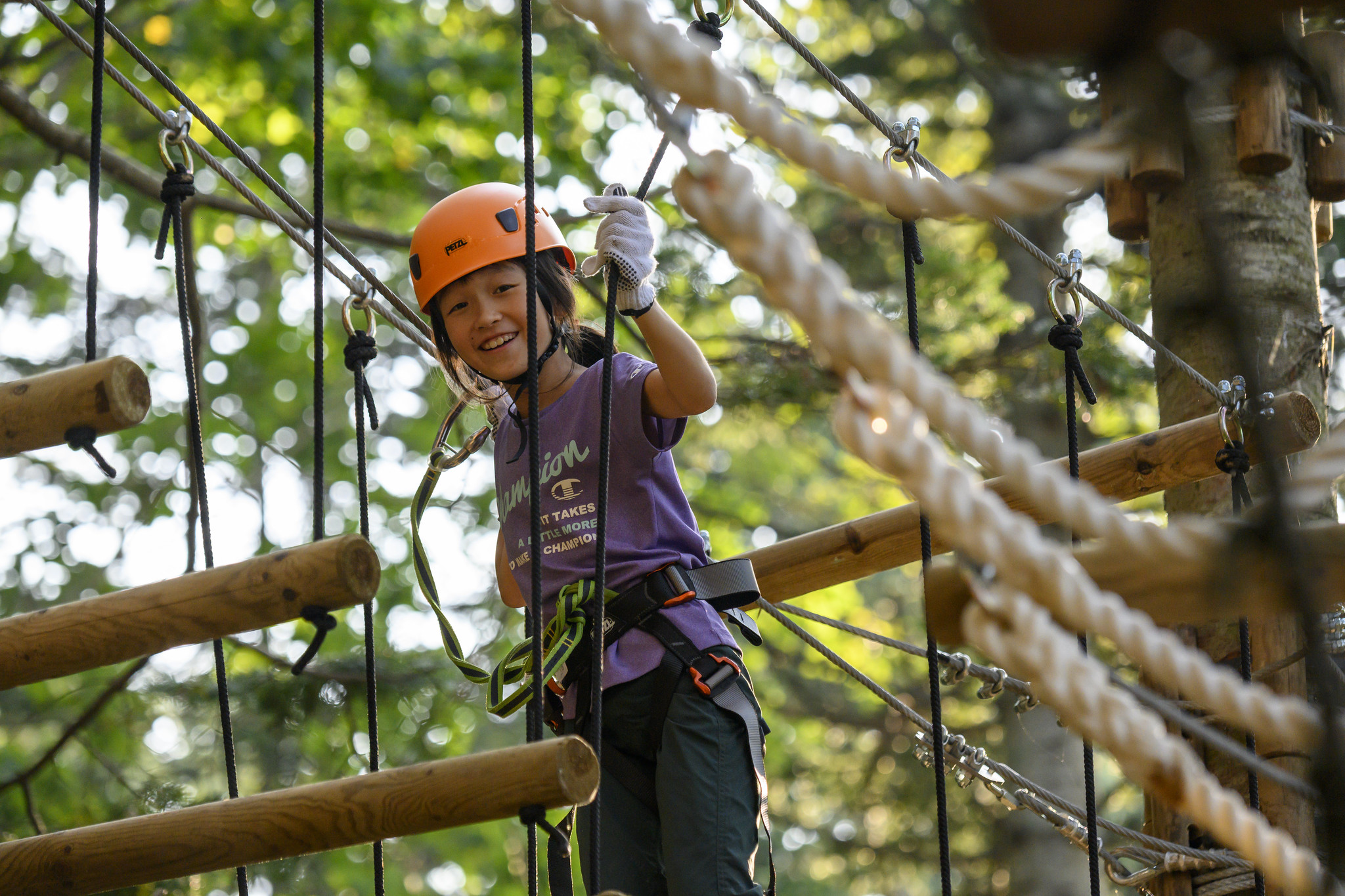 child tree trekking on a high ropes course in hanazono, niseko.